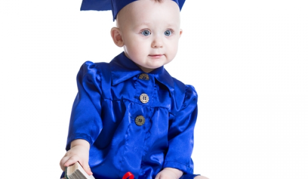 Picture of baby in cap and gown with diploma.
