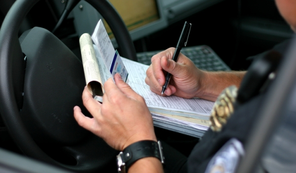 Police officer with criminal justice degree writing a speeding ticket.