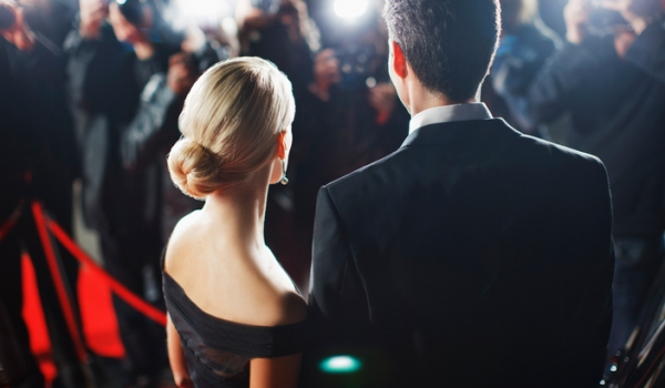 Celebrity couple on the red carpet with paparazzi around them.
