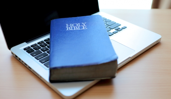 Blue Holy Bible on Laptop Computer