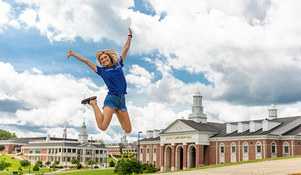 A Cumberlands student jumps into the air on campus