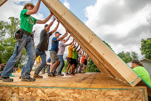Volunteers help set a wall on a MO house