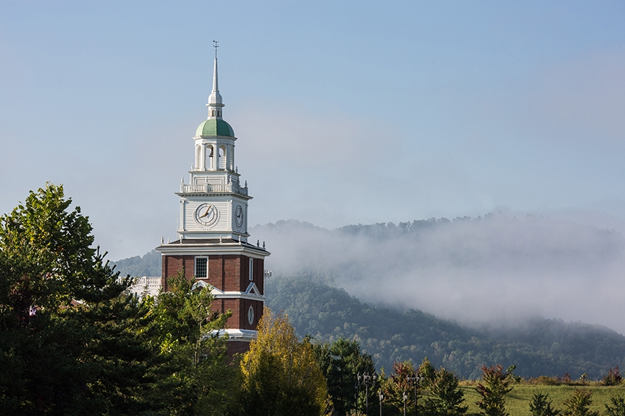 clock tower of business school and fog and mountains