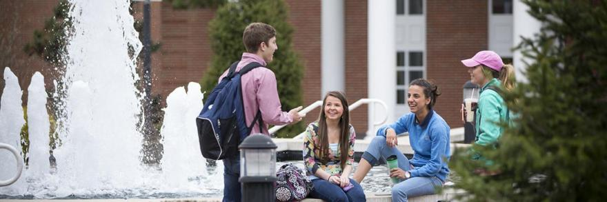 University of the Cumberlands students sitting at a fountain on campus talking and laughing.