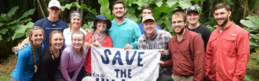 Group of people holding a sign during a study abroad session.