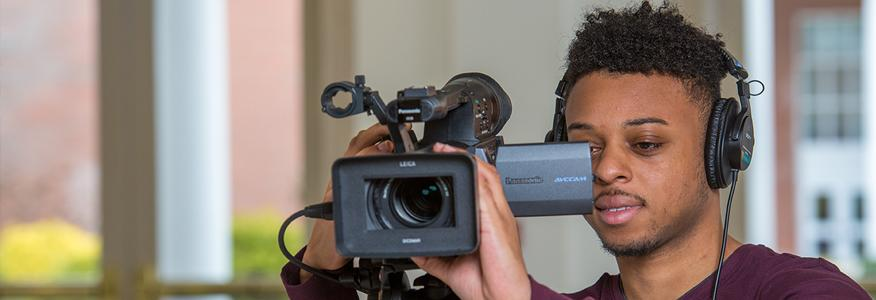 A communications major student working with a video camera.