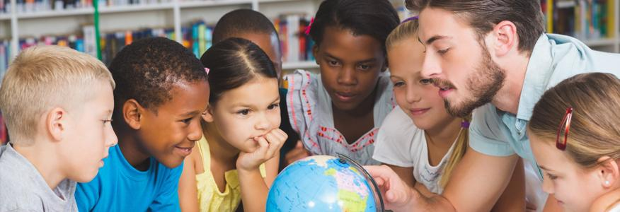 An elementary teacher with students pointing at a globe.
