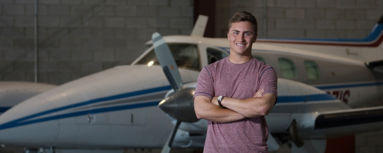 Guy standing in front of airplane