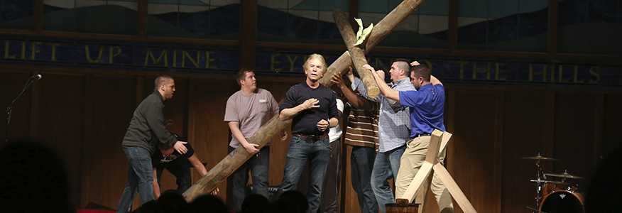 Bachelor in Christian studies degree students holding a wooden cross on stage during a sermon.