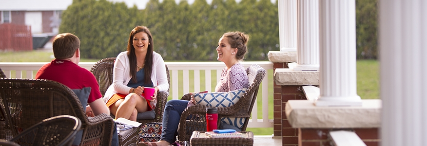 Three bachelor in psychology degree students studying together on a porch on the University of Cumberlands campus.