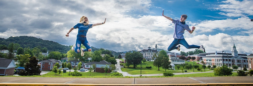 Students jump and high five in front of the Cumberlands campus